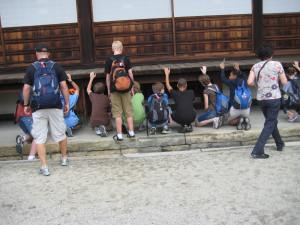 Minooka students peeking underneath Nijo Castle to see how the creaking floorboards work.