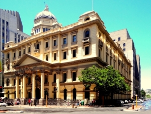 "Standard Bank building in Cape Town.  Jordan says, ""This building is of Anglo-Saxon design, as shown by its brick structure, similarities to Romanesque buildings, and its big design. It's similar to Romanesque because of its semi-round arches on some windows, thick walls, and symmetrical design. It is set apart from Romanesque of its brick composition and narrow windows.""  What do you all think?"